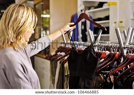 a young woman selects a little black dress from a rack of clothes in a fashion boutique