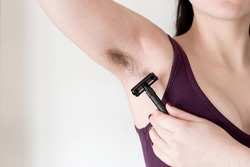 A young woman shaves her unshaved hairy armpits with a black stainless steel zero waste razor. Female hair removal concept. Selective close-up focus.