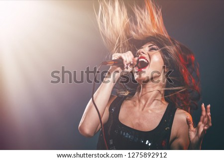 A young woman singer with tousled long hair holding a microphone and sing with a wide open mouth.