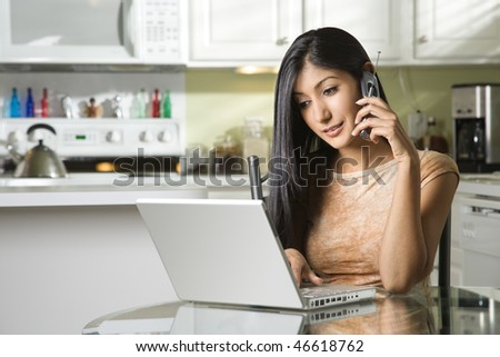 A young woman sits at the kitchen table using a laptop and talking on a cell phone. Horizontal shot.