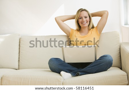 A young woman sits back on the couch with a notebook computer in her lap and her hands behind her head.  Horizontal shot.