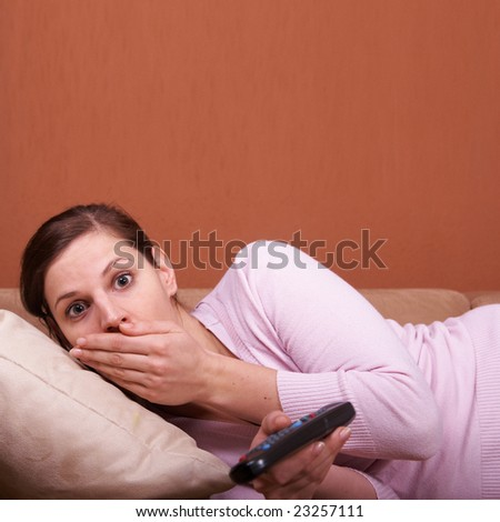 A young woman sits in front of a TV with the remote control in her hand on a couch. A lot of copyspace left. She seems to be shocked.