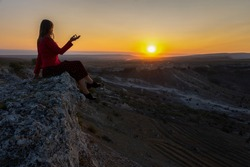 A young woman sits on the edge of a cliff, looks at the sun. A beautiful dark-haired girl poses in a dress against the background of mountains. Dawn in the mountains. The concept of unity with nature