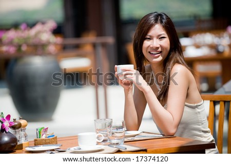 A young woman sitting alone at breakfast table at resort