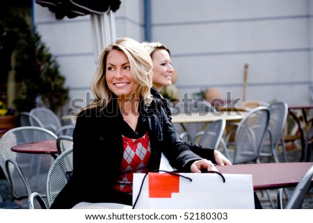 a young woman sitting at a sidewalk cafe