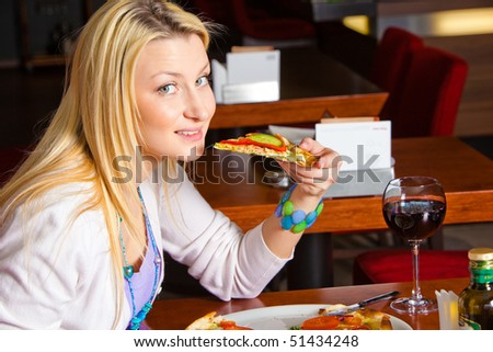 A young woman sitting in a restaurant. She is looking at the camera biting a slice of pizza. Horizontal shot.