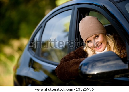 A young woman sitting in drivers seat of a saloon car