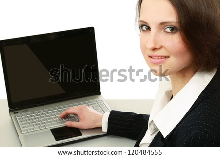 A young woman sitting in front of a laptop, isolated on white
