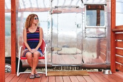 a young woman sitting next to a vintage camper