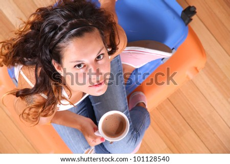 A young woman sitting on a stack of suitcases while drinking coffee and waiting for the departure to vacations.