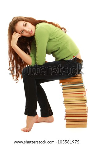 A young woman sitting on pile of books isolated on white background