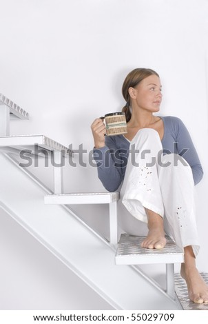 A young woman sitting on the stairs at home
