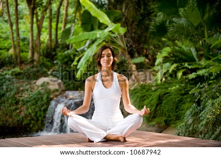 A young woman sitting outside in a yoga position looking very peaceful
