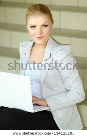 A young woman sitting with a laptop, isolated on white background