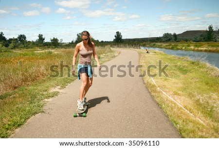 A young woman skateboards down a path near a river in Montana