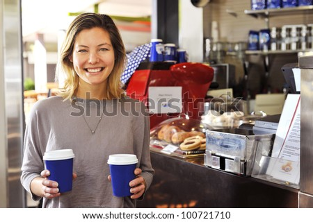 """a young woman smiles to camera as she walks away from the cafe counter carrying her two coffees, part of my """"cafe girl"""" series - stock photo"""