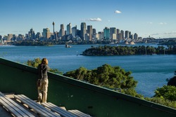 A young woman standing at the Sydney Zoo and enjoys the view to the skyline of Sydney City.