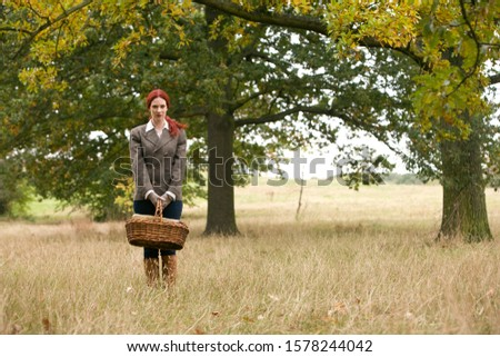 A young woman standing in a field, holding a wicker basket