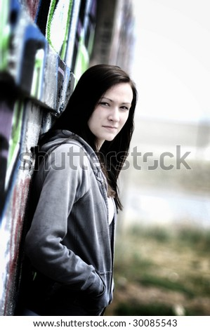 a young woman standing next to a graffiti wall