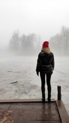 A young woman stands alone on a wooden bridge by the lake. Early cloudy foggy day. To be alone with yourself. Tight fog.