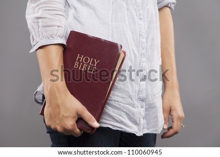 A young woman stands indoors casually holding a maroon bible to her side.