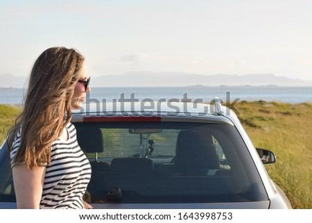 A young woman stands near the car and looks into the distance.