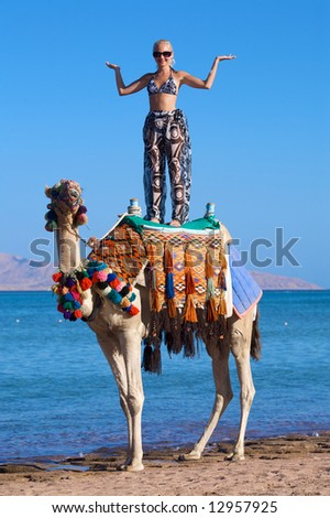 A young woman stands on a camel on the beach near the ocean.
