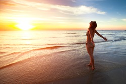 A young woman stands on the beach during a beautiful sunset, vacation vitality healthy living concept.