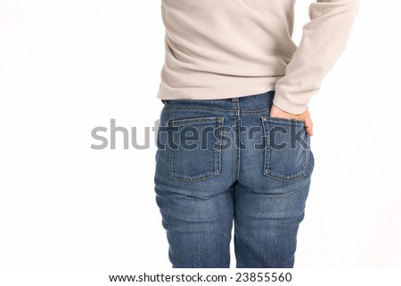 A young woman stands with her hand in her back pocket isolated on a white background.