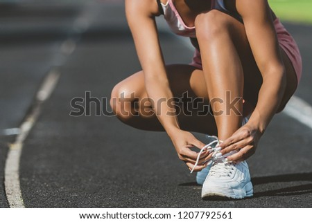A young woman stopped to tie a string while running in the stadium #1207792561