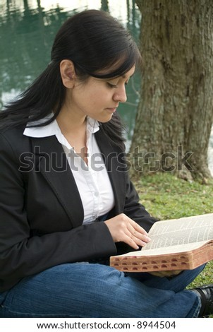 A young woman student sitting outside reading or studying a bible or book.
