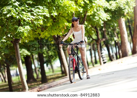 A young woman takes a rest from a bike ride in the park.