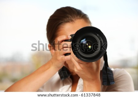 A young woman taking pictures over white background - stock photo