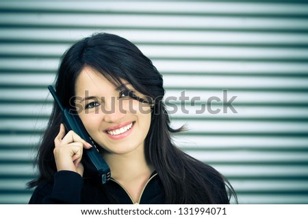 A young woman talking on a home wireless phone. color processed