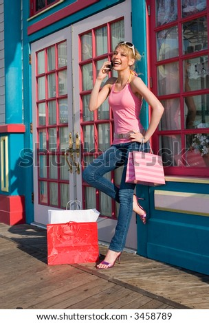 A young woman talking on her cellphone after a shopping spree