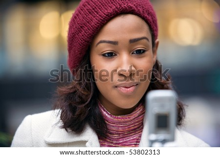 A young woman text messaging or checking something on her wireless phone.