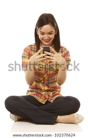 A young woman texting happily (on white)