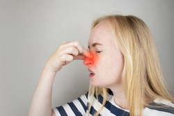 A young woman touches her nose, which is very painful. Medical care concept for difficulty breathing, clogged nasal passages and flu, colds or coronavirus