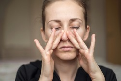 A young woman touches her nose with her fingers because of the loss of her sense of smell, does not feel the smell