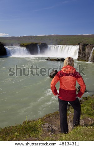 A young woman tourist by a waterfall. Shot on location at Godafoss waterfall in Iceland. The focus is on the woman in the foreground,