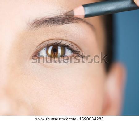 A young woman using an eyebrow pencil