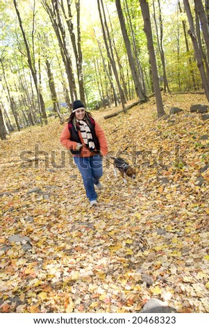 A young woman walking her dog through the woods.