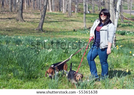 A young woman walking her two dogs in the park on a sunny day.