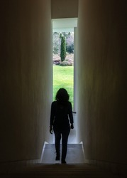 A young woman walks down a narrow corridor to a window overlooking nature