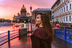 A young woman walks during a pink sunset in the center of St. Petersburg with a view of St. Isaac's Cathedr
