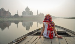 A young woman watching sunset over Taj Mahal from a wooden boat.