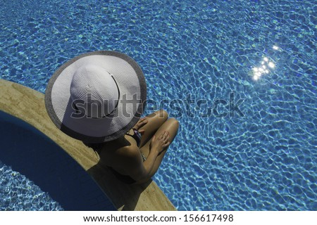 A young woman wearing a bikini and a white hat sits at the edge of a swimming pool. woman in a white hat sits by a pool