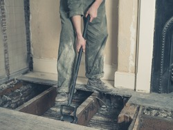 A young woman wearing a boiler suit is taken up the floor boards in a Victorian house