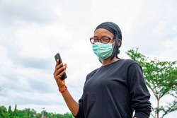 a young woman wearing a face mask holding up her mobile phone