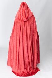 A young woman wearing a long red velvet cloak against a plain studio backdrop